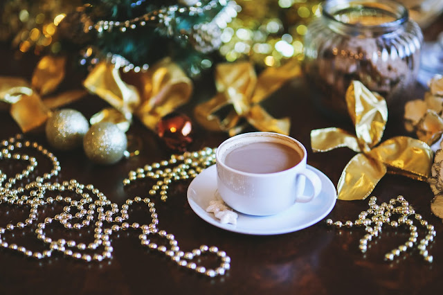 Christmas decorations and a cup of coffee over a wooden table.