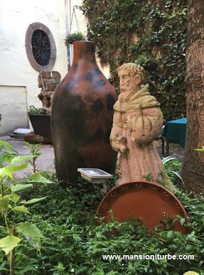 """Las Artesanías de Cantera, las podrás encontrar en la Región del Lago de Pátzcuaro. A las afueras de Pátzcuaro encontrarás varios talleres, así como en Tzintzuntzan y Patambicho, ambos con talleres a borde de carretera, por lo que son de fácil acceso para nuestros huéspedes en Hotel Mansión Iturbe que buscan de una escultura en cantera.   Nuestro amigo Andrew Carhartt, residente norteamericano en Pátzcuaro, nos comparte este artículo sobre la Cantera:   La piedra de Cantera es una roca volcánica relativamente ligera (en peso) encontrada solamente en México y América Central. Se encuentra en diferentes colores - incluyendo tonos verdes y negros - pero el más común es en el espectro gris-rosado. Es muy duradero y se ha utilizado durante siglos en México y América Latina en la construcción de iglesias, grandes casas y fuentes.   Michoacán es un lugar en donde puedes encontrar mucha cantera; Parece que hay  un gran abastecimiento de esta piedra y es trabajada de innumerables formas. En la época colonial se usaba principalmente en la construcción; ¡basta con mirar las iglesias alrededor del Estado!   - pero el uso más común actualmente está en hacer fuentes y figuras esculpidas.   Es tan poroso que si usted tiene una taza o un recipiente hecho de cantera (sin ningún sellador), se puede verter casi cualquier calidad de agua en ella, y el agua purificada se gotea por el fondo (haciéndola potable), dejando los residuos detrás.  Especialmente en la zona de Tzintzuntzan viniendo de Pátzcuaro, hay innumerables  artesanos que trabajan cantera. Justo antes de entrar en Tzintzuntzan de Pátzcuaro,  por ejemplo, hay un verdadero """"centro comercial de cantera"""" con varios cientos de metros  de figuras, grandes y pequeñas, que puedes observar desde ambos lados de la carretera,  que llamarán tu atención.   Si puedes resistir la seducción de ese lugar para pararte a comprar o admirar las artesanías  en cantera, prosigue por este Pueblo Mágico que es Tzintzuntzan y continúa hacia Quiroga."""