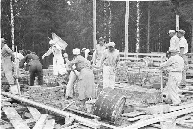 Mustavalkoinen kuva. Miehiä ja naisia rakennustyömaalla. Naiset pukeutuneina hameisiin ja esiliinoihin. Miehillä housut ja paita päällä.