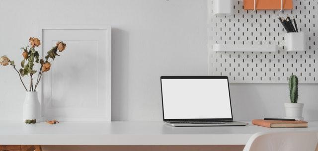 White laptop on white table.