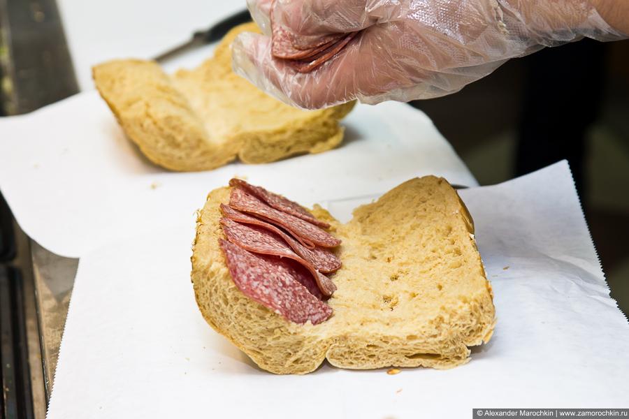 Приготовление сэндвича. Салями раскладывается на разрезанную булочку