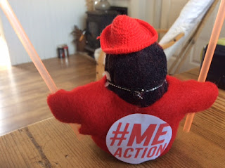 MEme a small stuffed penguin which is Corina Duyn's alter ego, is ready for action for M.E.  wearing a red tshirt with the Action for ME logo