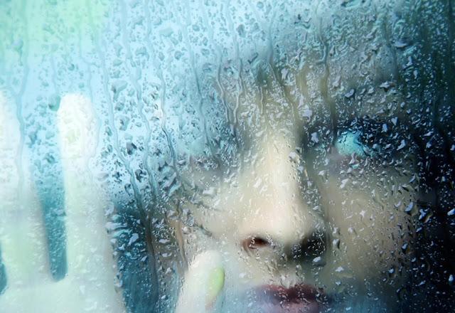 femër në dritare të lagur