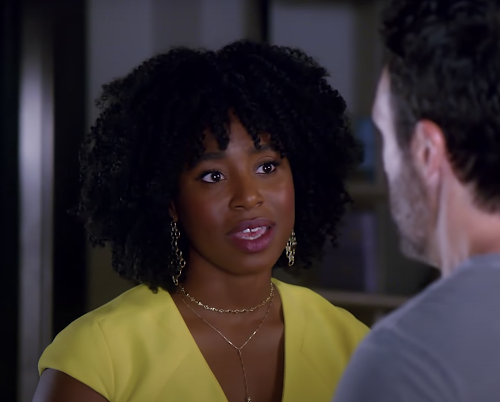 Kirby Howell-Baptiste in Why Women Kill. Kirby is wearing a bright yellow dress and gold jewellery.
