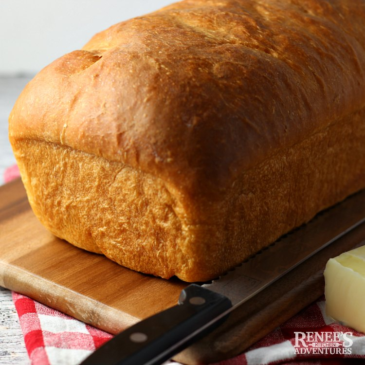 Whole loaf of soft white bread on a wooden board with knife ready to be sliced