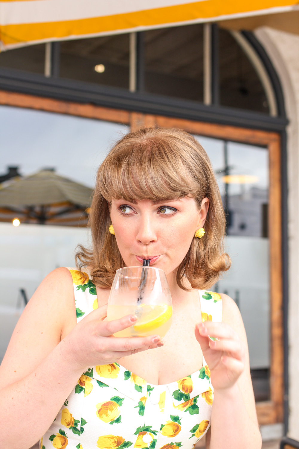 Liana of @findingfemme drinks a gin and bitter lemon at Mitchell Harris in Ballarat in yellow floral.
