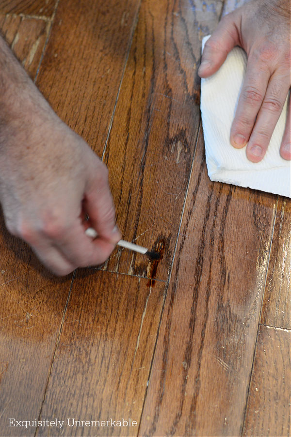 Using A q-tip to apply stain to a wooden floor chip