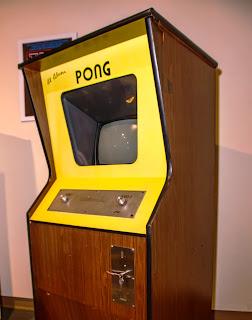 Fotografía de la máquina recreativa de Pong (1972). Se trata de un mueble de madera en forma de prisma cuadrangular cortado oblicuamente por el centro para mostrar un panel amarillo en donde un cristal transparente recuadrado deja ver, tras él, una pantalla de televisión. Debajo del marco transparente hay otro panel metálico con dos controladores en forma de rueda que puede girar en ambos sentidos. La parte posterior inferior recta del mueble tiene un orificio para insertar monedas