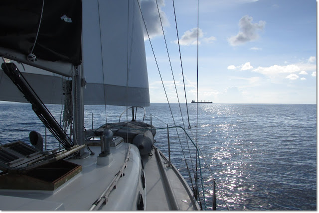 A 36' sailboat points towards the horizon crossing the gulf stream.