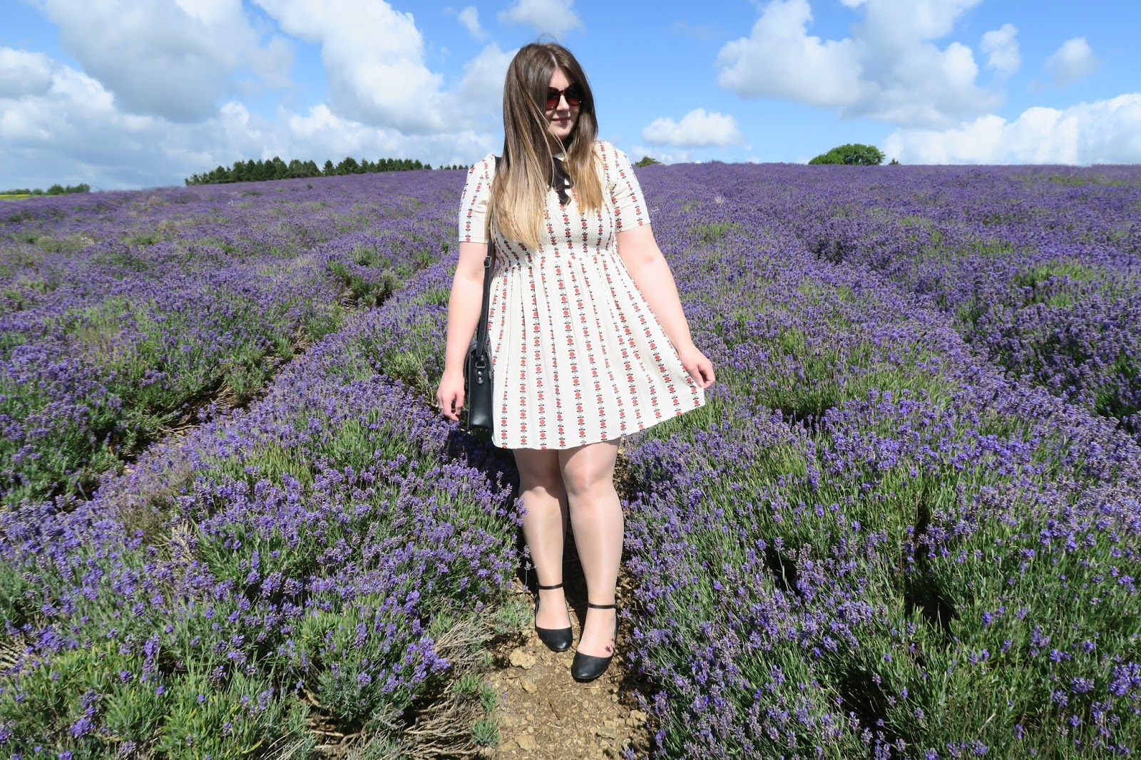 Grace wearing a white dress standing in the centre of a lavender field