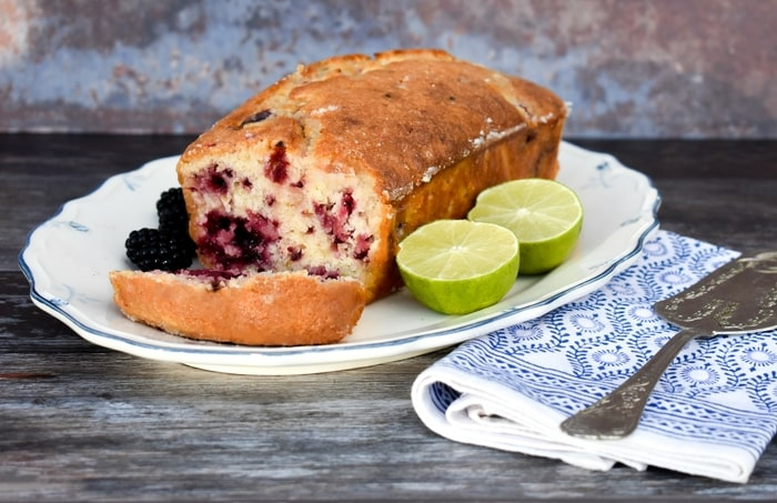 Vegan blackberry lime drizzle loaf cake on a white platter with blackberries and lime halves