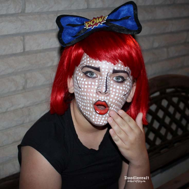 Pop art comic book girl cosplay with red wig and facepaint pixel dots for comic convention costume.