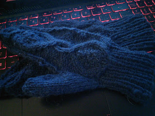 Two cabled mittens laying on top of one another, knit in a dark blue dk-weight yarn.