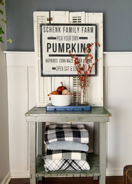 Side table with blankets on bottom shelf.