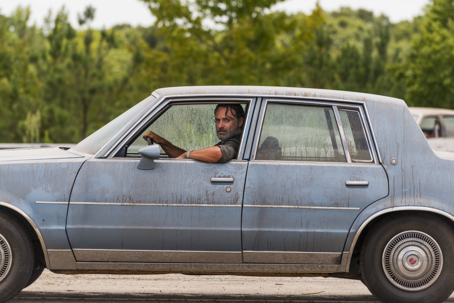 Rick Grimes, en un coche en el episodio Rock in the Road de The Walking Dead