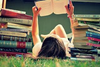 petite fille qui lit dans l'herbe
