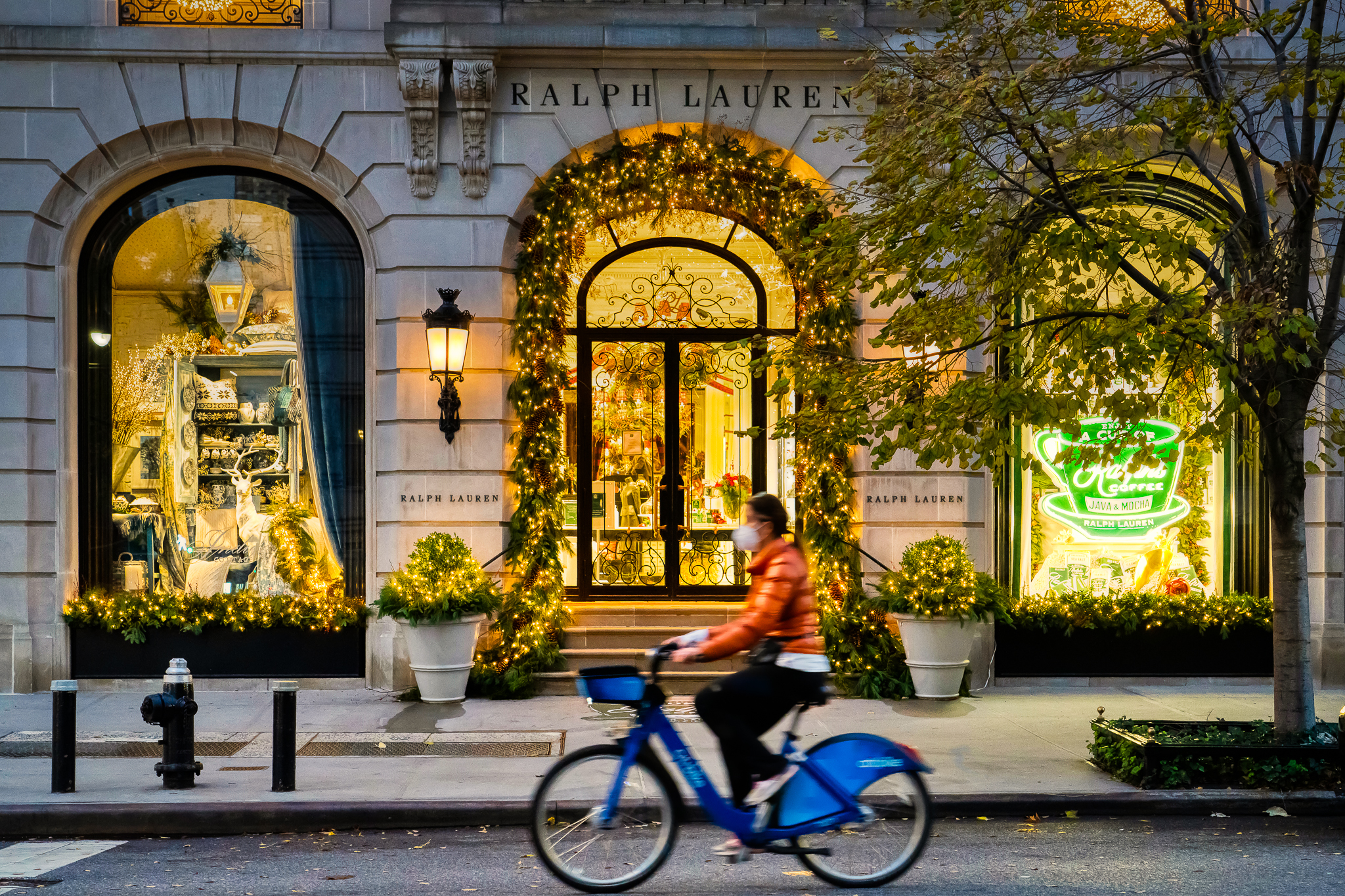 a photo of a cyclist riding past christmas decoractions in new york city