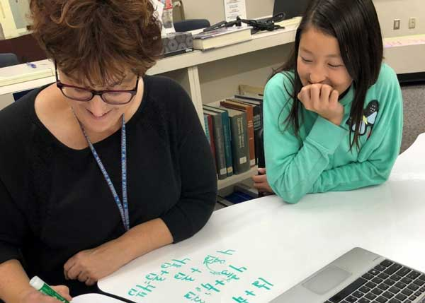 Math teacher helps girl on white board table working on mastery challenge