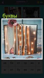 стоит книга подсвечена огнями и рядом стоят буквы 667 слов 7 уровень