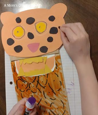 gluing on black spots for jaguar paper bag puppet
