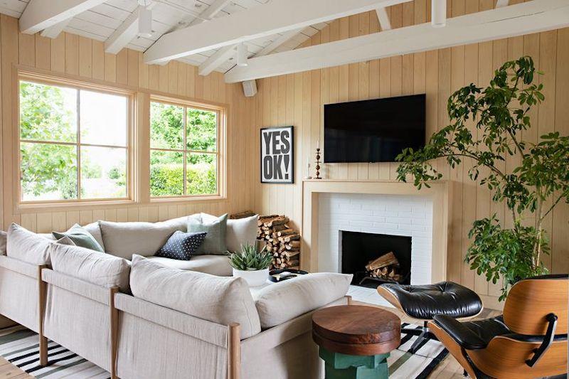 Zona de sofás, tv y chimenea en casa de campo