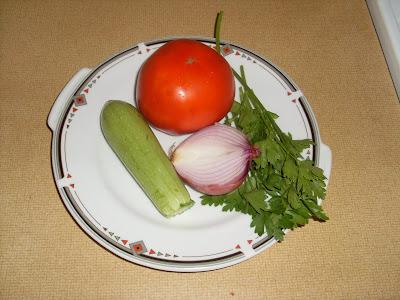 Πιάτο που έχει μισό κρεμύδι,μια ντομάτα ενα κολοκυθάκι και λιγα κλωνια μαιντανού