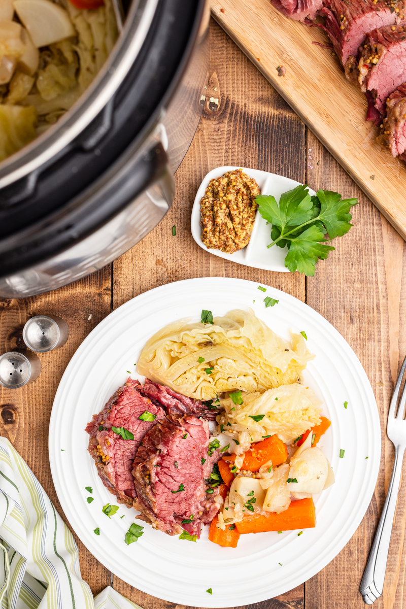 Overhead photo of cooked Keto Instant Pot Corned Beef and Cabbage on a white plate.