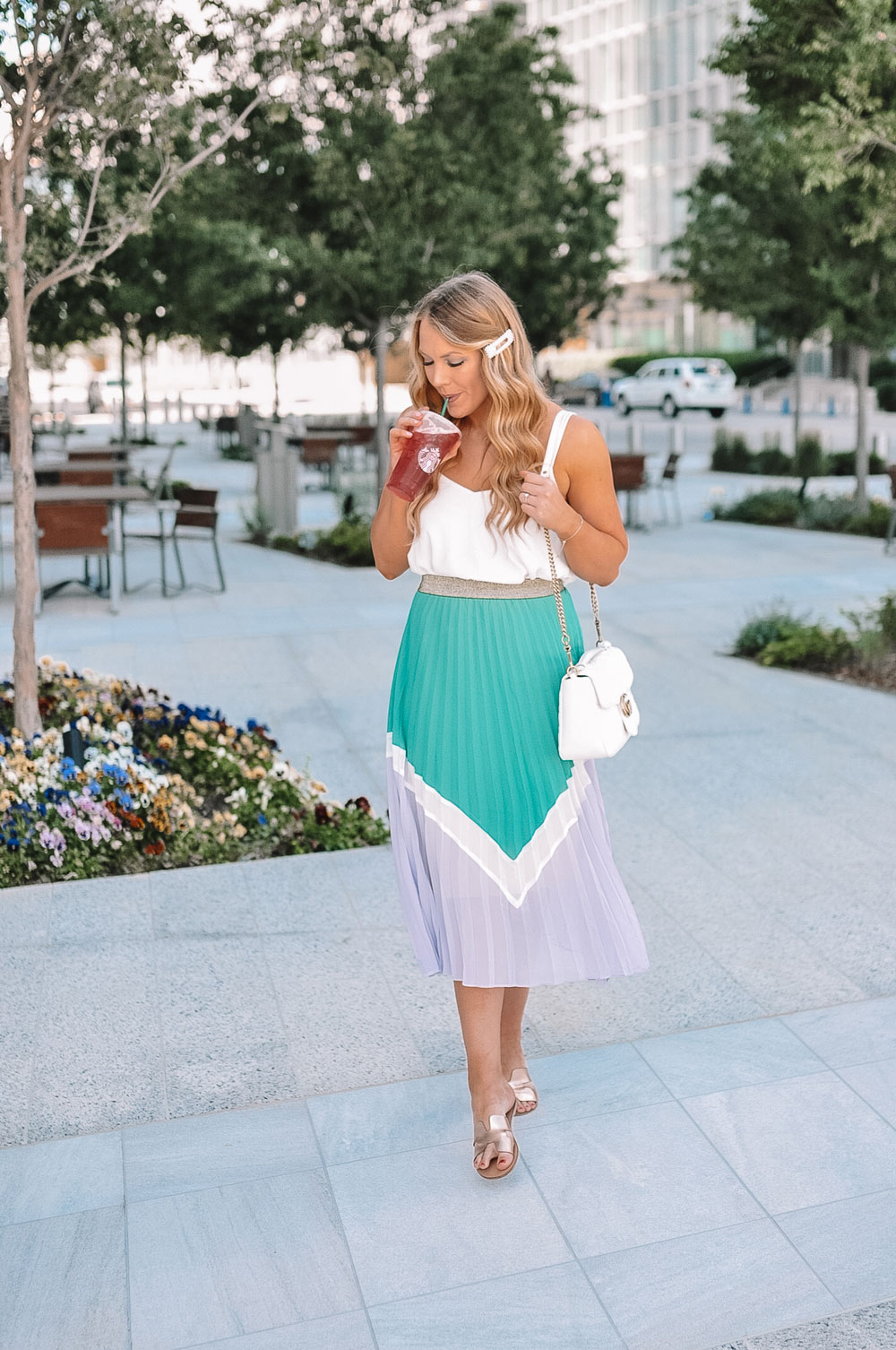 OKC Blogger Amanda Martin wearing a pleated skirt and Swarovski bracelet while sipping her Starbucks