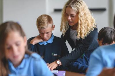 Elever med likartade kläder i skolbänkarna, kvinnlig lärare böjd över elev och pekar i läroboken.