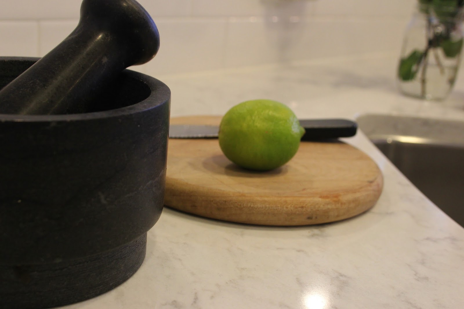 A black mortar and pestle, rustic wood board, and lime on a quartz countertop in the kitchen. #minuet #whitequartz #viatera