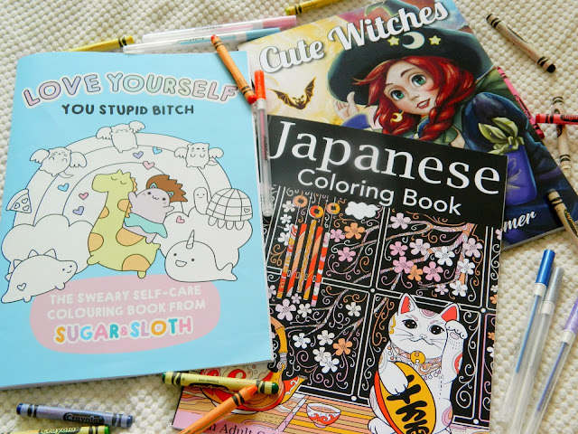 A photo showing three colouring books: cute witches, japanese colouring book, the sweary self-care colouring book from Sugar & Sloth