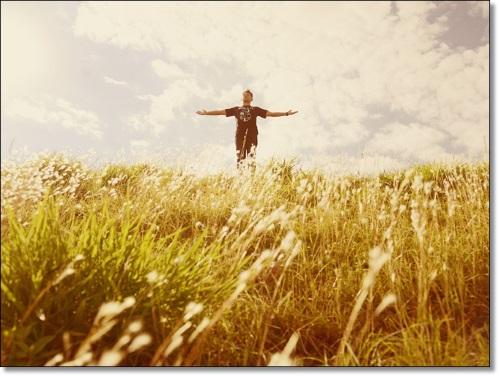 Um jovem de braços abertos em um vasto campo de trigais, como se estivesse agradecendo a Deus.
