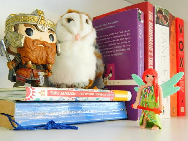 A photo showing a shelf of books, with an owl plush, a funko pop of Gimli and a Lego fairy