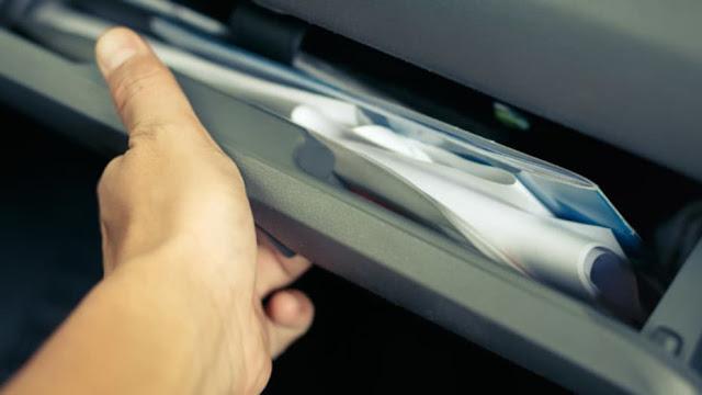 Persona cogiendo papeles del coche