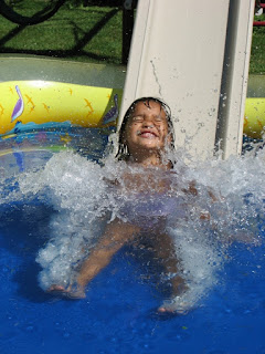 Image of child sliding down a small water slide