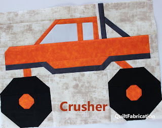 orange monster truck with 1 exhaust pipes
