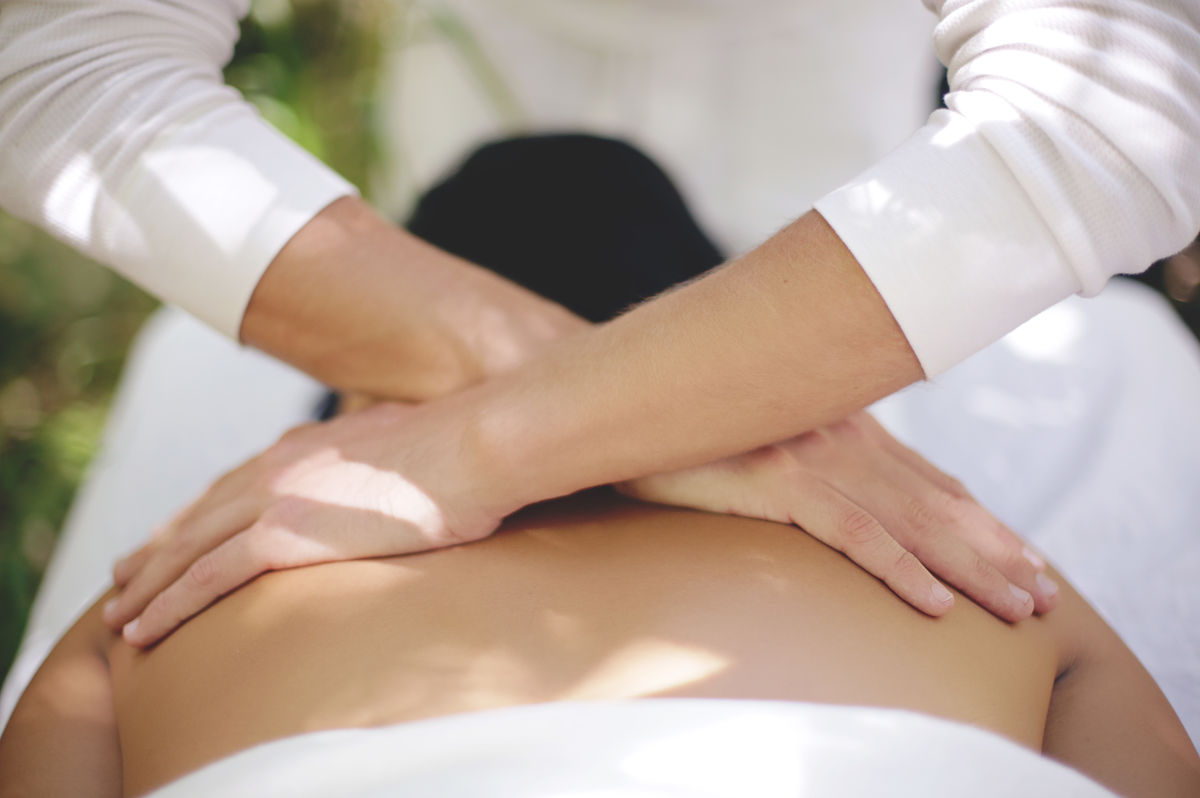 A Myofascial Release Therapist performing cross-hand shears on a client's back.