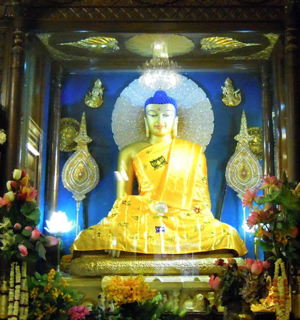 A gilded stone statue of the Buddha inside the shrine room (garbagriha) of the Mahabodhi Temple, Bodhgaya. It was probably made during the Pala period (c. 1100 CE).