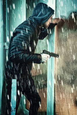 لص يحمل سلاحا بيده يحاول اقتحام أحد الأبواب
