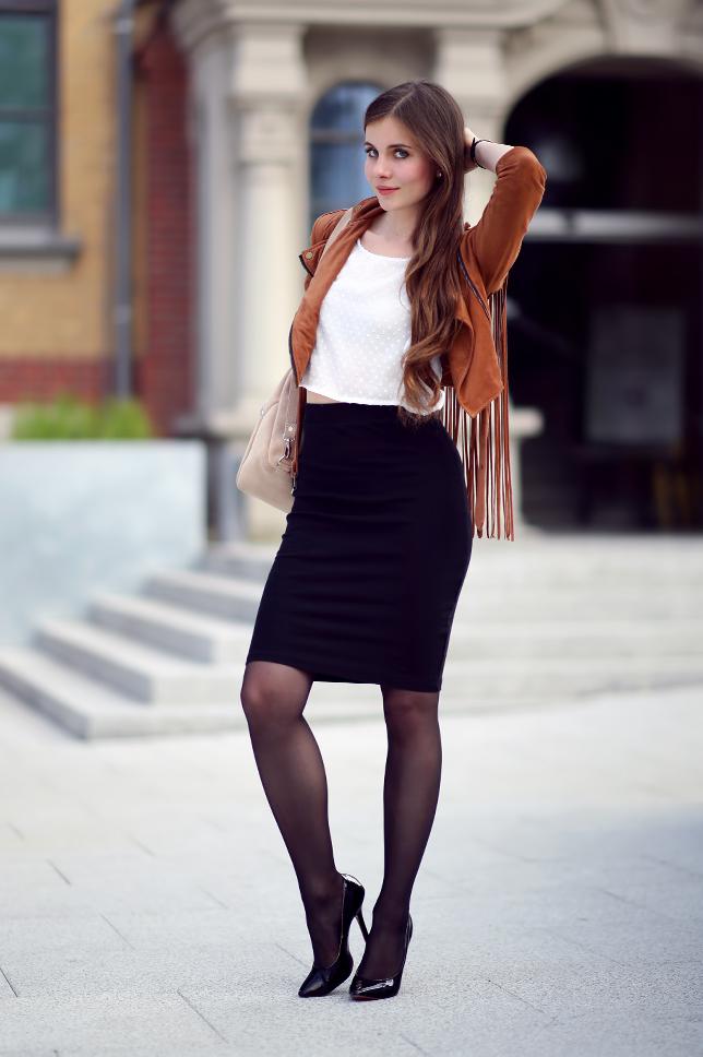 Brązowa kurtka z frędzlami, czarna ołówkowa spódniczka, czarne rajstopy i beżowy plecak