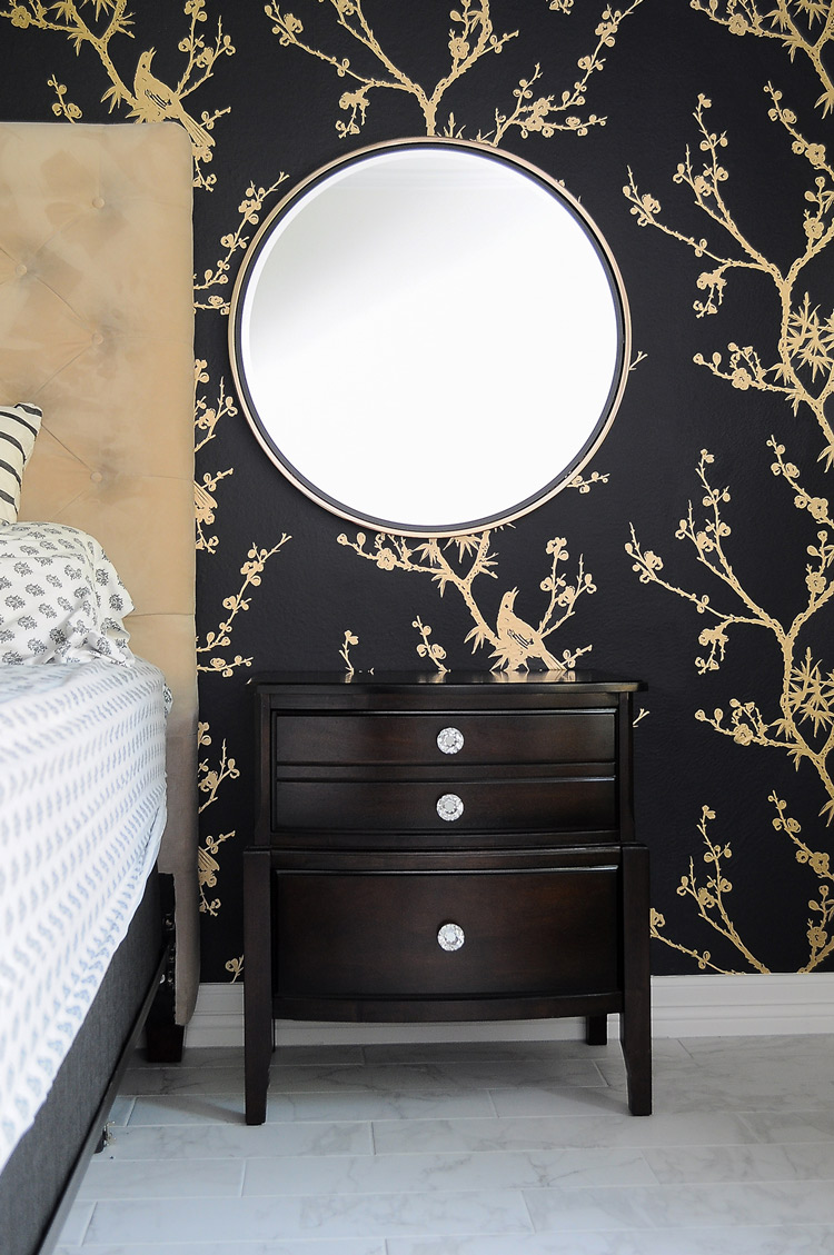 How to hang mirrors over a pair of nightstands to make sure they're even- love her simple tips and directions. The Wais mirror by Holly & Martin adds a touch of glamour to this dramatic black and gold master bedroom. Simply stunning! The wallpaper is bird watching by Cynthia Rowley for Tempaper.
