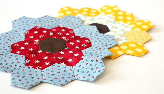 Angled view of two overlapping heaxagon flower quilt blocks, one in red and blue and the other in yellow and white, on a white background.