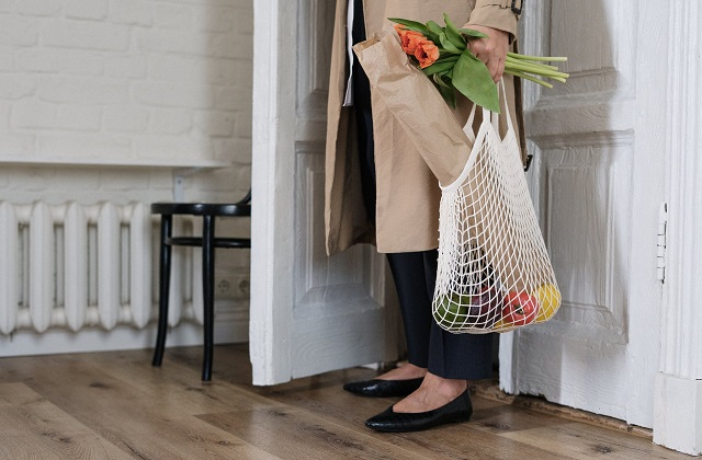 woman behind door wearing trench coat holding flowers and basket