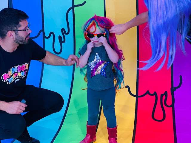 A 3 year old in a rainbow wig and sunglasses standing in front of a rainbow backdrop with an adult each side styling her