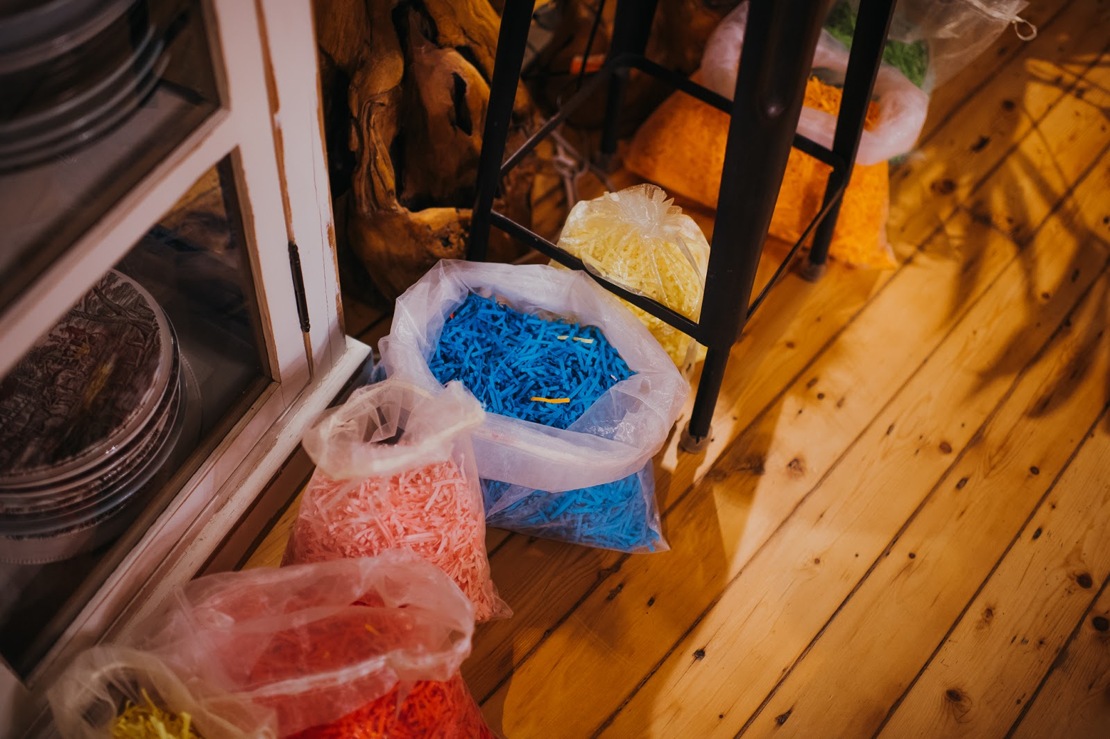 A row of bags each including a different colour of shredded paper. (Blue, pink, orange, yellow and red.)