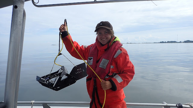 Henkilö pelastautumispuvussa roikottaa vedenalaista videokameraa veneessä
