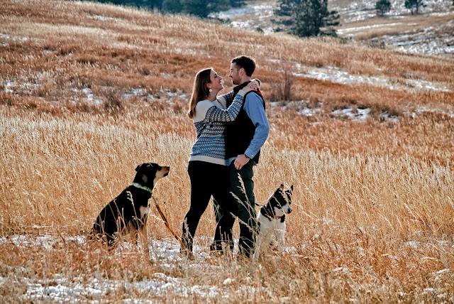 a woman put her arms around her fiance for an engagement photo in Boulder Colorado in a grassy meadow