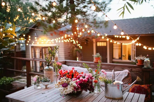 A wooden table in the foreground with flowers and a metal watering can on it . In the background are lights in the tree and a light-colored house with the windows lit up.