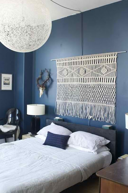 bedroom with blue wall and large macrame