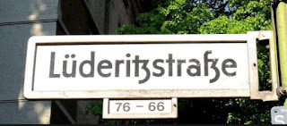 "Lüderitzstraße, named after Adolf Lüderitz nicknamed ""Lügenfritz"" or lie buddy who ""bought"" land from native Africans until he claimed to own the entire coastal strip from South Africa to Angola, 220,000 sq miles."